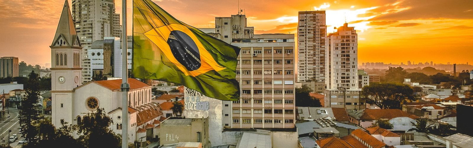 The sun behind buildings and the Brazilian flag flying in foreground